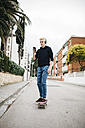 Spain, Torredembarra, young man with headphones standing on skateboard looking at his smartphone - JRFF000446
