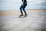 Spain, Torredembarra, young skateboarder in front of the beach, partial view - JRFF000449