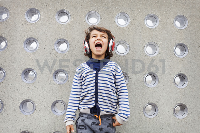 Portrait of little boy singing while listening music with headphones - VABF000154
