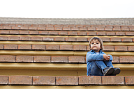 Portrait of little boy sitting on steps of an open-air theater - VABF000160