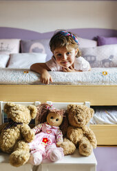 Portrait of little girl lying on bed with  toys in the foreground - MGOF001437