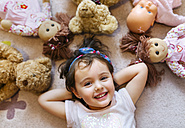 Portrait of smiling little girl lying on the floor with teddies and dolls around her - MGOF001443
