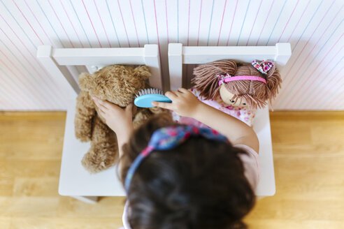 Little girl playing with her teddy and doll, seen from above - MGOF001446