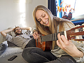 Young couple at home making music - LAF001611