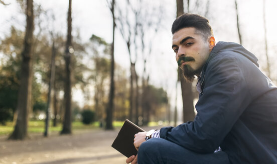 Portrait of bearded young man with book in the park - MGOF001449
