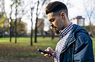 Young man looking at his smartphone in the park - MGOF001452