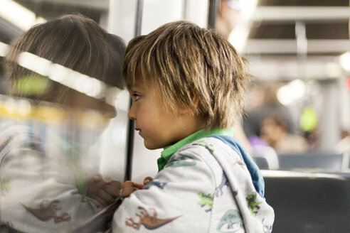 Little boy looking through window of a subway train - VABF000163