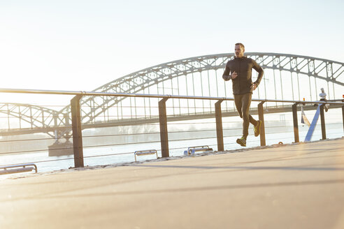 Germany, Cologne, Young man running at the riverside - MADF000806