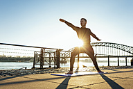 Germany, Cologne, Young man practicing yoga at the riverside - MADF000812