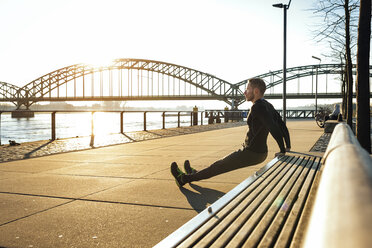 Germany, Cologne, Young man doing push ups on bench - MADF000815