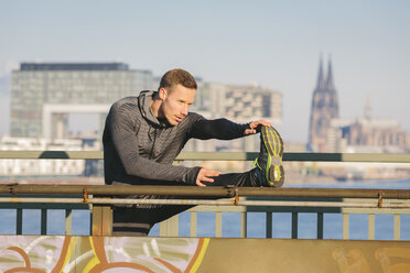 Germany, Cologne, Young man worming up for workout - MADF000818