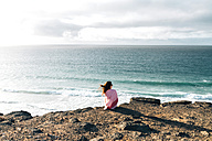Spain, Fuerteventura, El Cotillo, back view of woman looking to the sea - GEMF000732