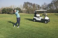 Golfer on a golf course, golf cart - ABZF000210