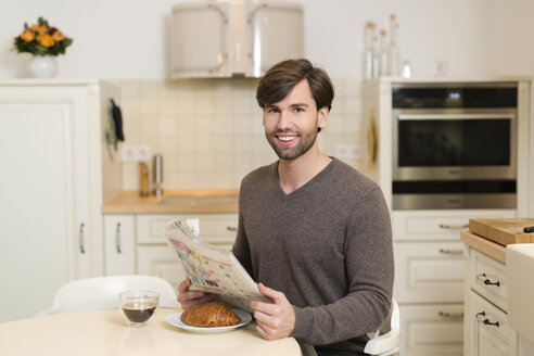 Portrait of smiling man sitting at breakfast table with newspaper - SHKF000494
