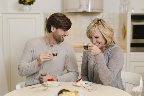 Mother and adult son drinking espresso in the kitchen and having fun together - SHKF000497