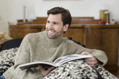 Portrait of smiling man sitting on the couch with a book - SHKF000500