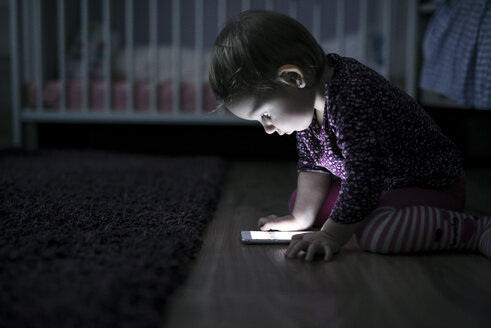 Toddler sitting on the floor playing with smartphone - HAPF000236