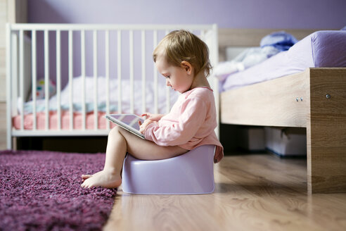 Toddler sitting on potty playing with digital tablet - HAPF000239