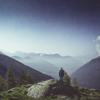 Italy, Lombardy, Chiesa in Valmalenco, man standing on a rock  at morning light - DWIF000701