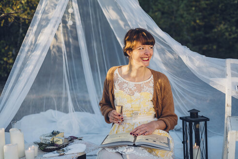 Portrait of laughing woman with book and glass of champagne in a romantic camp in nature - MJF001728