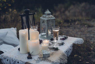 Two glasses of champagne, storm lamp and lighted candles on lace - MJF001734