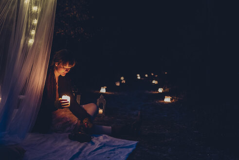Woman in a romantic camp lighted  by candle light in nature - MJF001740