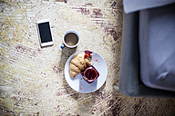 Smartphone, cup of coffee and croissant with jam on the floor - FMKF002276