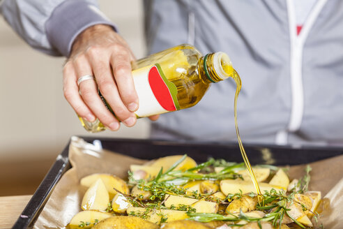 Pouring oil over potato wedges on baking tray - FMKF002294