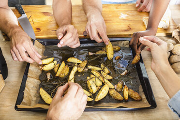 Friends eating potato wedges from baking tray - FMKF002306