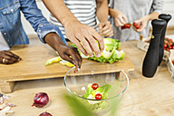 Hands over salad bowl in kitchen - FMKF002309