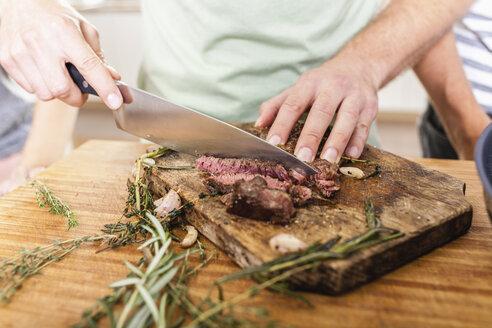 Cutting steak on chopping board - FMKF002336
