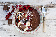 Bowl of banana chocolate smoothie with red currants and grated coconut - SARF002567