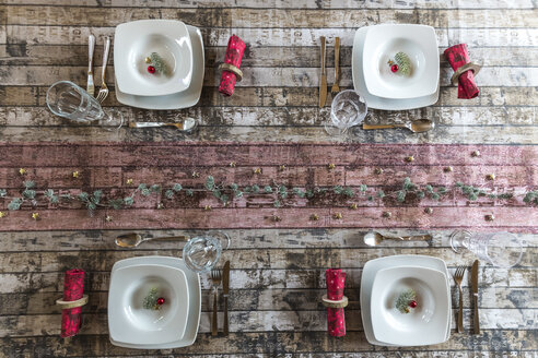 Four place settings on laid table at Christmas time - SARF002570