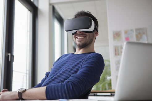 Smiling man wearing Virtual Reality Glasses in the office - RBF004087
