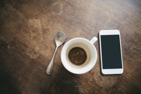 Coffee cup with remains of coffee, spoon and smartphone on wood - EBSF001233
