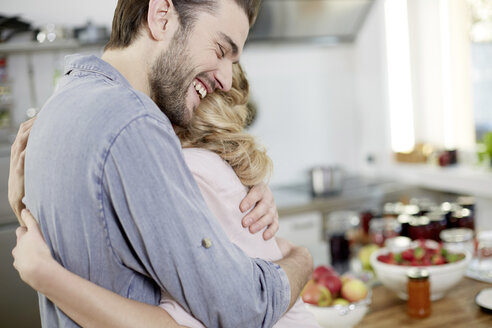 Happy couple hugging in kitchen - FMKF002405