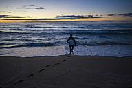 Spain, Barcelona, surfer at sunrise on the beach - SKCF000062