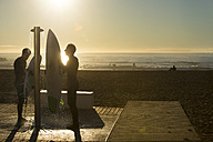 Two surfers at sunrise on the beach, shower - SKCF000068