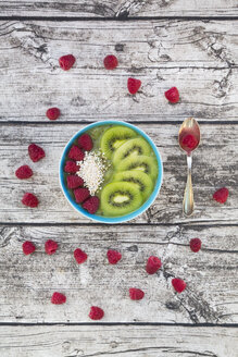 Bowl of kiwi apple rocket smoothie with chia seed, popped amarant, kiwi slices and raspberries - LVF004556