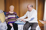 Senior man checking blood pressure of his wife at home - GEMF000741