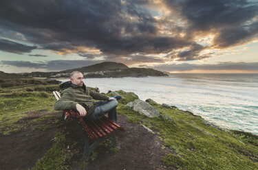 Spain, Ferrol, man sitting on a bench at the coast looking at distance - RAEF000905