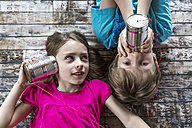 Portrait of brother and little sister playing with tin can phone - SARF002580