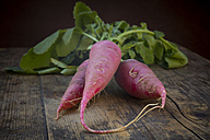 Organic red radish on dark wood, close-up - LVF004565