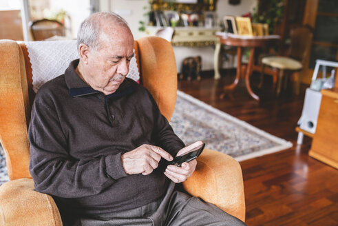 Senior man sitting on armchair at home using smartphone - GEMF000744