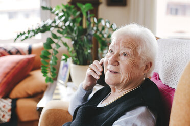 Portrait of smiling senior woman telephoning with smartphone at home - GEMF000750