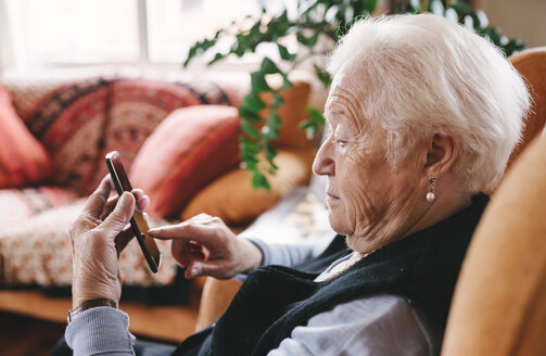 Senior woman sitting in the living room using smartphone - GEMF000753