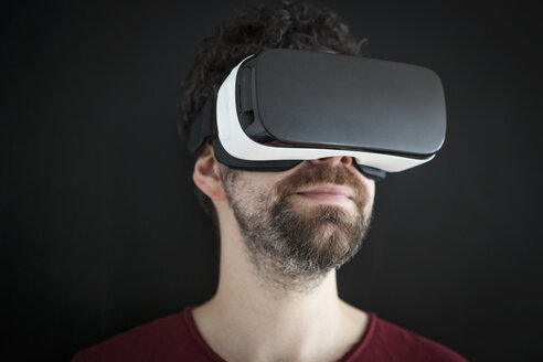 Smiling man wearing Virtual Reality Glasses in front of black background - RBF004095