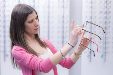 Woman in an optician shop choosing glasses - ERLF000139