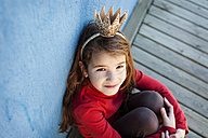 Portrait of little girl with a crown leaning against blue wall looking up to camera - VABF000209