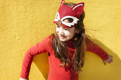 Portrait of little girl with animal mask in front of yellow wall - VABF000212